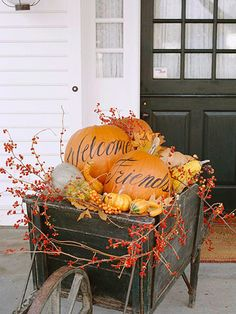 """Fill a wooden wheelbarrow with gourds, pumpkins, dried leaves, and berry sprigs. Work with a variety of shapes and colors to achieve a vibrant look that captures the essence of fall. Paint a """"welcome friends"""" message on two large pumpkin and place on top of the wheelbarrow. Weave artificial berry vines around the wheelbarrow for a splash of stunning red Halloween Porch Decorations, Outdoor Decorations, Autumn Decorations, Thanksgiving Decorations Outdoor, Fall Decorations For Outside, Wedding Decoration, Outdoor Thanksgiving, Decoration Noel, Outdoor Ideas"""