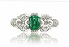 AN ART DECO EMERALD AND DIAMOND BROOCH. The central cushion-shaped emerald, weighing approximately 14.85 carats, flanked by four circular-cut diamonds, to the diamond-set geometrical plaque, 1920s, 6.7 cm