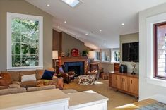 Living room with plenty of windows that provide natural lighting, preventing the living room from appearing too small because of the slanted ceiling