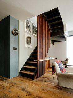 Лестница на второй этаж закрыта от жилой комнаты вертикальной решеткой из деревянного бруса. .