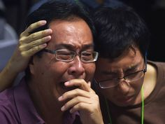Family members of passengers onboard the missing Malaysian air carrier AirAsia flight QZ8501 react after watching news reports showing an unidentified body floating in the Java sea, inside the crisis-centre set up at Juanda International Airport in Surabaya.