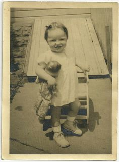vintage photo of a toddler girl with her doll circa 1945 - 1955.