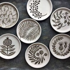 gray and white ceramic plates with botanical art