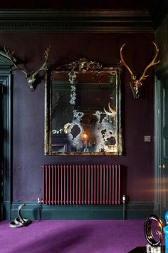 an enchanting hallway with luxurious antique mirror and animal horn wall decor with gloomy purple wallpaint and carpet