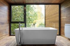 Contemporary bathroom interior design in a 1970s house remodel in Quebec city, Canada. The ceiling lenght windows enlighten the room with natural light while the wooden planks give a warm feel and highlight the beautiful squared bath. www.parka-architecture.com