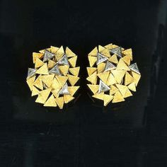 A pair of diamond and gold earclips, by Andrew GRIMA, 1970, designed as a cluster of overlapping textured triangular plaques, set randomly with triangular-shaped diamond detail (hva)
