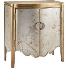 Metallic silver and gold-finished wood cabinet with painted scroll detail and a scalloped apron.    Product: CabinetConstruction Material: WoodColor: Metallic silver and goldFeatures:  Scroll and feather detailingCurved apron Dimensions: 36.25 H x 32 W x 16.75 D