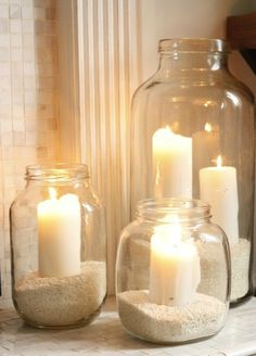 Glass jars + sand + white candles. Pretty for summer