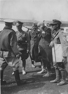Generalfeldmarschall Erwin Rommel (second from left) speaking with Italian generals at an airport in North Africa. Rommel's personal Fieseler Fi 156 Storch can be seen in the background.
