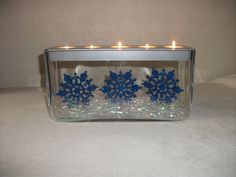 Partylite Customizable Centerpiece decorated for Christmas with glittery snowflake ornaments and iridescent grass from Dollar Tree. Ornaments are taped to the bottom of the tealight holder.
