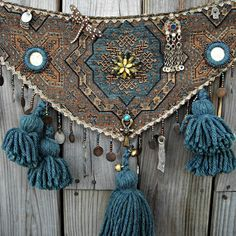 Tribal belly dance belt tassel belt tribal fusion with evil eyes, shisha, and moon faces. Moon Dancer by Loreli Tribal tassel dance belt of tapestry fabric in muted blue and gold. Accented with hand beaded happy moon faces, jeweled evil eye and hamsa charms, Ankh charm, kuchi dangle, jeweled dragonfly, hand done shisha mirrors, Indian coin, and tiny faux tusk. Center back of belt motif is accented with a jeweled decoration in complementary colors. Lower edge of belt is edged in hand beaded…