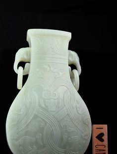 """A pale celadon archaistic jade vase, 18th. c., Kangxi - Qianlong, Beijing Imperial Workshop, of flattened HU form with elephant head handles and suspended rings, carved in relief with an interwoven stylized pattern of archaic dragons, below a wide wavy band under the rim, stone of even translucent light celadon color. 8 1/2"""" h., 21.8 cm. <br><br>Provenance: -Collection of Count Primor Alsocernantoni -Louis Von Cseh of New York City -1963 July 16th Christies New York. Lo..."""