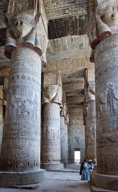 "[EGYPT 29513] 'Outer hypostyle hall of Hathor Temple at Dendera.' The columns in the outer hypostyle hall (or pronaos) of the Hathor Temple at Dendera are crowned by four-sided capitals carved with the face of the cow-eared goddess. The faces symbolize the four cardinal points of the universe and stress the universal character of the sky goddess Hathor, who was also called ""Lady with the four Faces"". The square structure that is placed on top of the actual face is a ..."