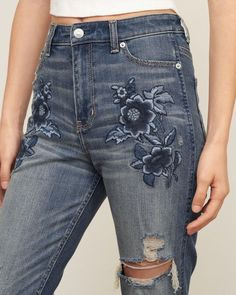 Slightly cropped above the ankles with frayed cuffs, featuring medium washed  denim with fading and whiskering, floral…