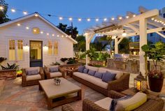 Farmhouse Patio with outdoor kitchen under pergola, seating area and string lighting. Patio flooring is red brick and slate tile #patio Torrey Pines Landscape Co. Inc