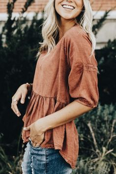 A burnt orange peplum top and distressed denim; casual and pulled together.