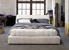 Padded bed frame with visible seam, headboard stuffed with goose down.   Comfort and elegance guaranteed!