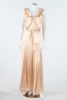 A couture bias cut oyster satin gown, early 1930s. with pleated detailing to bodice and skirt, with a note attached stating it was bought at 'Clair Soeurs Paris in 1930', tie belt with facetted crystals