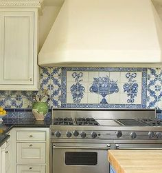 European-Inspired Backsplash ~ Blue-and-white backsplash tiles were the basis for the classic color scheme and timeless European feel of this Arizona kitchen. The ornate pattern above the range makes the backsplash a focal point. The rest of the backsplash pattern was borrowed from the detail of the design above the cook top. ~
