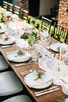 Uncovered wooden table set with a runner of vintage crocheted doilies, blush floral centerpieces in silver vessels and place settings of vintage china. Image by Ken Kienow. #wedding
