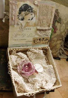 In an old cigar box...I really enjoy finding creative displays like this with lace, flowers and other vintage items...then tie they together with a theme.