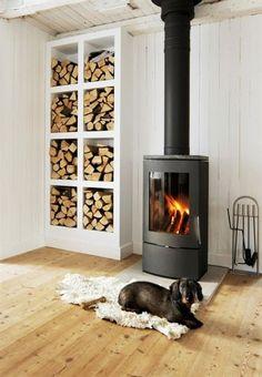 <strong>Varm plats</strong><br>Den platsbyggda vedhyllan rymmer mycket ved. Det eldas flitigt i den danska braskaminen i gammaldags stil från Jydespejsen.