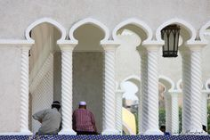 Two men take a sit in the beautiful architecture of Sultan omar Ali Saifuddin Mosque