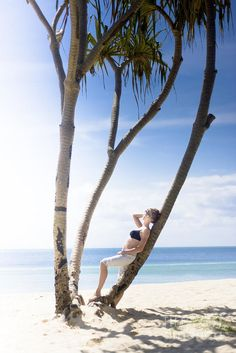 A Female Tourist Enjoying The Sun Whilst Leaning On A Palm Tree On A Tropical Beach With Blue Ocean Behind by Ryan Jorgensen