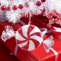 """Easy candy ornaments 12 4"""" Styrofoam disks Mod Podge 2 paintbrushes, small and medium Red acrylic or tempera paint 12 toothpicks Scissors 12 6"""" x 8"""" cellophane bags 24 twist ties 2 small bowls Glue Silver glitter 2 yards ribbon, ¼"""" wide, optional Tape"""
