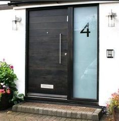 Welcome! The black metal/wood Cottage front door (example pictured) is to be installed using a right hinge on a low threshold. The Cottage door viewer and mail slot will be installed at an accessible height and the door handle is to be a lever style. All are satin nickel. The sandblasted glass window suggested for the left side of the Door will include a stenciled street address, as pictured.