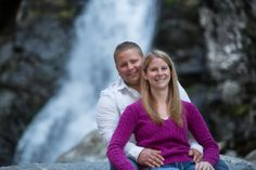 A couple sitting in front of a waterfall. Copyright Photographics Solution 2013