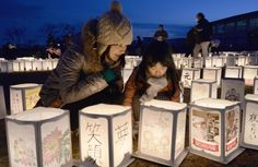 A mother and her daughter attend a candle-lighting event held Sunday to commemorate the third anniversary of the March 11 tsunami and earthq...
