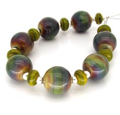 "Lampwork Beads FHFteam UK SRA - ""Loam"" Green Purple Blue Glass rounds. £23.50, via Etsy."