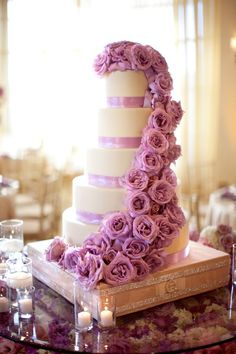 While the cake itself is simple, these cascading roses make this pastry almost too pretty for guests to eat! #purplewedding #cakes #roses