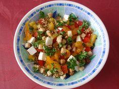 Salade met quinoa, rode en gele paprika, gedroogde abrikozen, feta kaas, pecannoten, croutons, peterselie en een dressing van olijfolie met knoflook, citroen en agavesiroop.