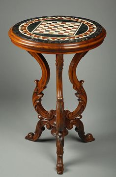 An Italian top marble inlaid resting on a wood sculpted tripod table...