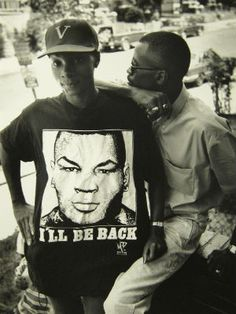 """This fashion staple has stuck around through the Great Depression, when T-shirts were first worn as undershirts and issued to military servicemen. In the latter part of the 20th century, T's became a way to protest, send messages or show your political affiliations. In this 1993 photo, a woman wears her boyfriend's """"I'll Be Back"""" T-shirt, a T that popped up around the time Mike Tyson went to prison in 1991.  RELATED TAGS"""