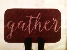 This gather welcome mat, rug or carpet in dark red with the cursive text 'gather' is the perfect winter themed item to place at your doorstep. It's perfect for enhancing your Christmas or holiday home decor, as a winter housewarming gift or to surprise your family when you come home for the holidays.     Don't miss out! THERE'S ONLY ONE LEFT so order before it's gone!     Our rugs are hand painted with precision and act as a rustic, yet refined accent in your home. We pride ourselves on…