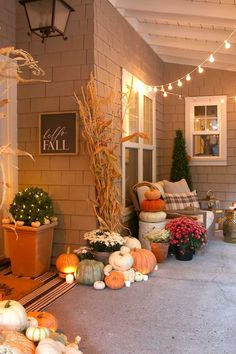 Cozy and natural fall porch decorating ideas. Create a welcoming front porch using pumpkins, cornstalks and candles.