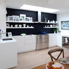 Monochrome scheme that manages to avoid the clinical minimal look. By incorporating family photographs standing proud against the black wall together with white crockery and touches of green and adding a traditional wooden table and chairs. this modern room has touches of character giving it a more interesting persona and rounding those sharp contemporary edges, metaphorically speaking.