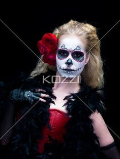 portrait of a scary female posing against dark background. - Portrait image of a female wearing scary sugar skull make-up posing against black background. Model: Christine Vandenberk