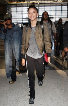 Zendaya gave her jet-setting style a tomboy-ish charm with black Adidas trackpants that she styled with a gray tee and a green bomber.