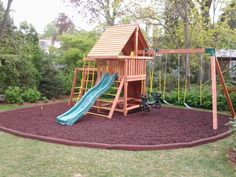 Dream swing set with rounded rubber mulch area.