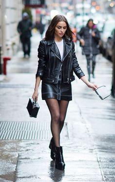 Olivia Culpo usa conjunto em couro de saia e jaqueta, t-shirt branca e ankle boots.