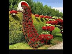 Pic: Garden art: Cascading flowers in pot growing over hedge. From the vertical garden board Topiary Garden, Garden Art, Garden Design, Diy Garden, Garden Paths, Amazing Gardens, Beautiful Gardens, Beautiful Flowers, Red Flowers