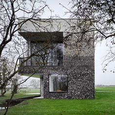 Flint House features rugged stone walls that gradate from smoky grey to chalky white.
