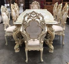 SILIK BAROQUE STYLE, HANDCRAFTED IN ITALY, DINING ROOM TABLE AND CHAIRS WITH A CRACKLE FINISH, GOLD TRIM AND HAND PAINTED FLORAL MOTIF., THIS PIECE HAS VERY ORNATE CARVINGS AND RAISED SWAG AND SCROLLWORK THROUGHOUT. THE BEVELED EDGE TOP IS PROTECTED BY GLASS AND THE LEGS COME TOGETHER IN THE CENTER WITH A HEAVY SUPPORT BAR ACCENTED WITH FLOWERS IN THE MIDDLE. THERE ARE 8 CHAIRS, INCLUDING TWO WITH ARMS. THEY ARE FINISHED IN A LUXURIOUS IVORY AND CHAMPAGNE TAPESTRY FABRIC WITH GOLD THREADING…