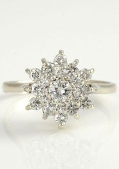 Vintage 1.50 carat total weight diamond ring, circa 1950. The ring is set in 14 karat white gold with a round 0.25 carat center diamond VS1 clarity I color and 18 surrounding round diamonds at 1.25 carat total weight VS1-SI2 clarity H color. Size 8.25.
