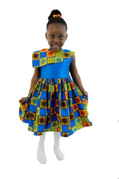 A square patterned ankara African Print girls dress with a cape in front and at the back. A blue satin material makes up the top part of the dress.  The cape has been brought to live with silver studs. This little dress has so much love infused into it.  Ooh did you know the studs glitter at night?  Just what your little girl needs to truly stand out and get all the attention.