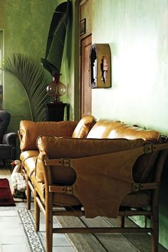 lovely leather lounge. and lovely light. love the mossy-colored walls.